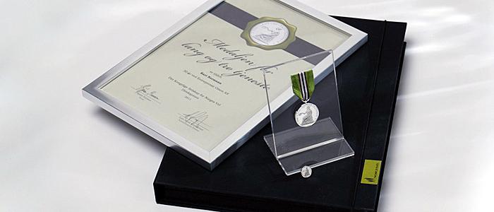 Medaljepakken med Medaljen for lang og tro tjeneste, jakkemerke, stativ, diplom og gaveeske