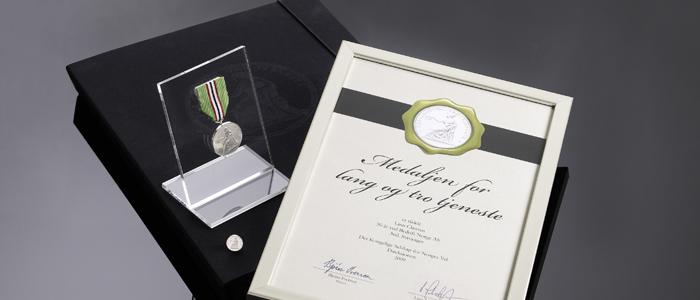 Medaljen for lang og tro tjeneste leveres i en flott eske sammen med jakkemerke, diplom og stativ for å stille ut Medaljen