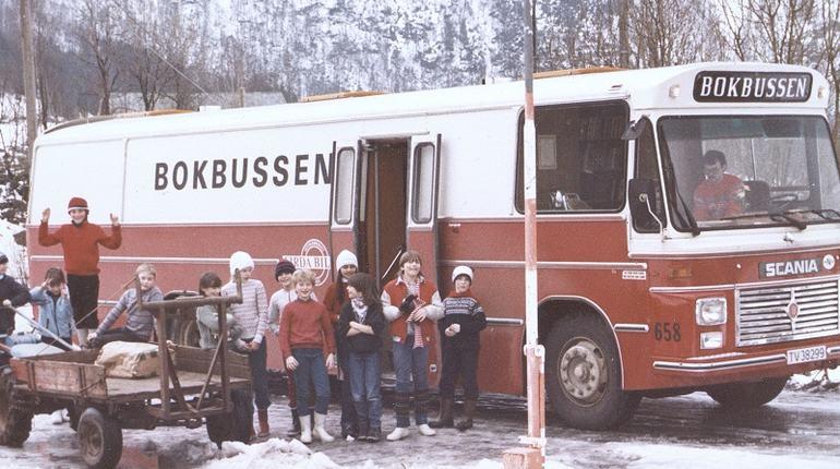 Bilete av gamal buss med ei gruppe med born framfor. Vinterlandskap.