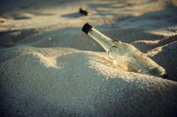 Glassflaske i sand