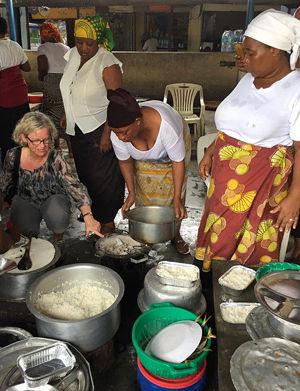 Prosjektleder Jorunn Tønnesen sammen med kvinner som lager mat på biobriketter