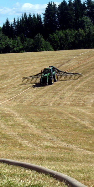 Traktor på jorde med slangespreder for biogjødsel