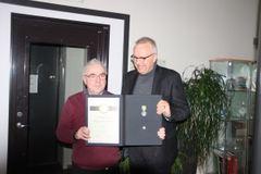 Odd Stikbakke ble hedret med Medaljen for sin innsats ved NSB. Regiondirektør Øivind Leet stod for overrekkelsen.
