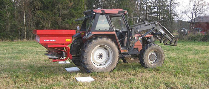 Traktor med bakker som måler mengden gjødsel for riktig innstilling av sprederen