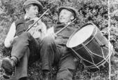 To unge menn ligg på bakken i gras/krattskog med sixpence-luer og kvar sitt instrument, ein med fele og ein med tromme.
