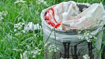 Plast i søppelbøtte i natur
