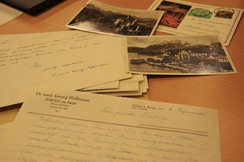 Brev og postkort ligg spredt ut over eit bord.