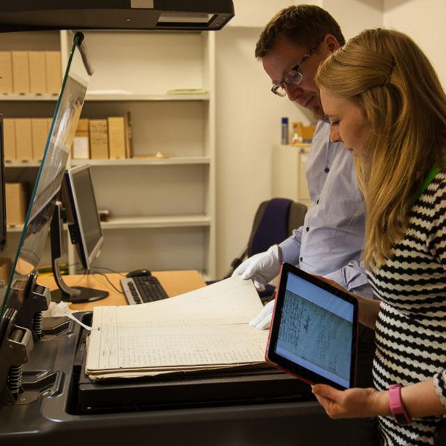 bilete av mann og kvinne som scannar gamal protokoll på bokscannar. Kvinna har også ein i-pad som viser digital versjon av protokollen.