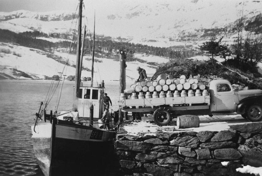 Bilete i svart/kvitt av båt som tek imot mjølkespann frå ein lastebil på land.