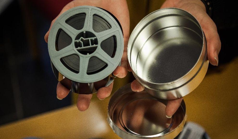 To hender held fram ein open rund boks i blikk med eit mikrofilmband opp i.