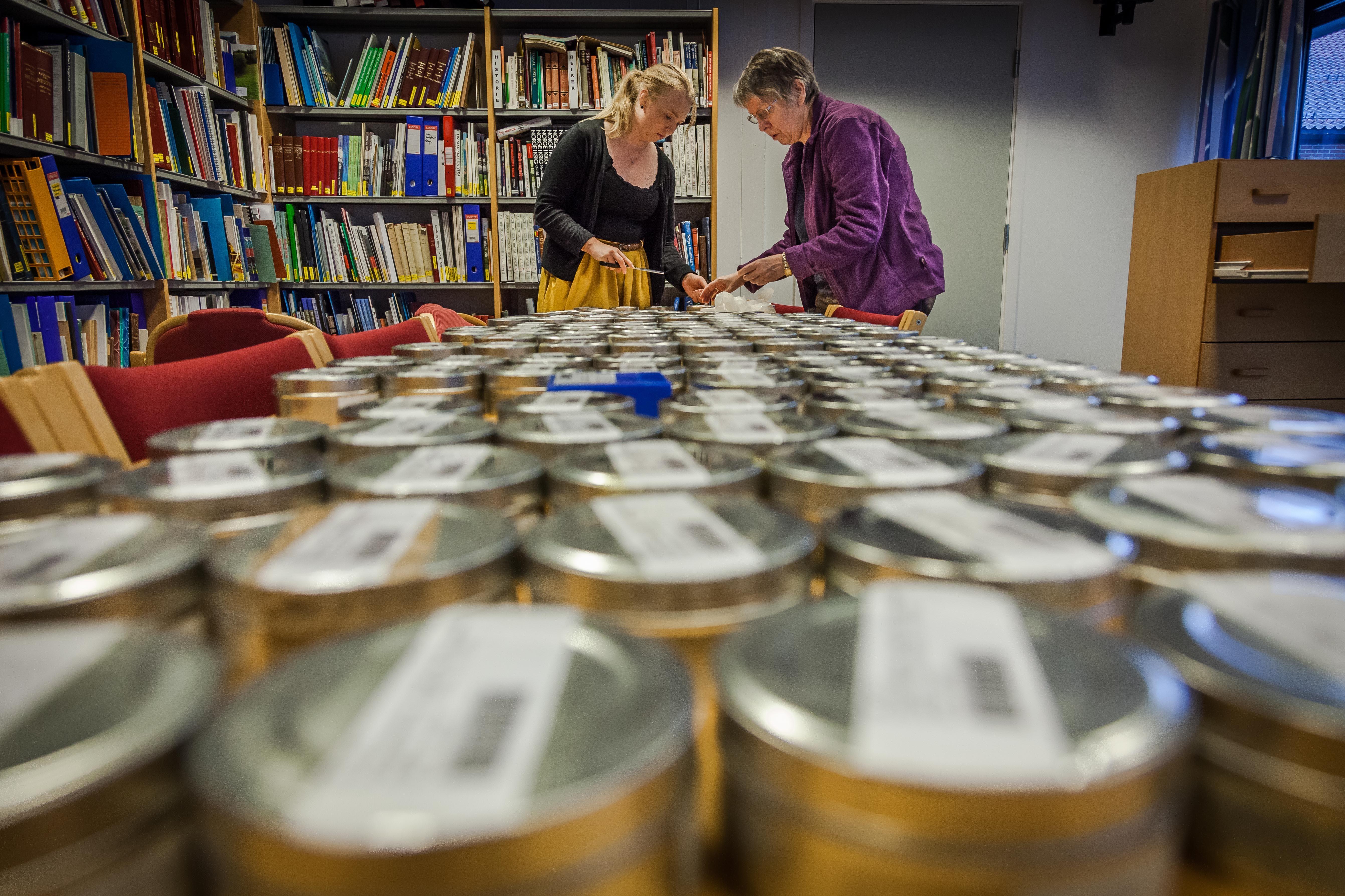 Runde blikkboksar med mikrofilm står ut over eit bord. To kvinner arbeider i bakgrunnen.
