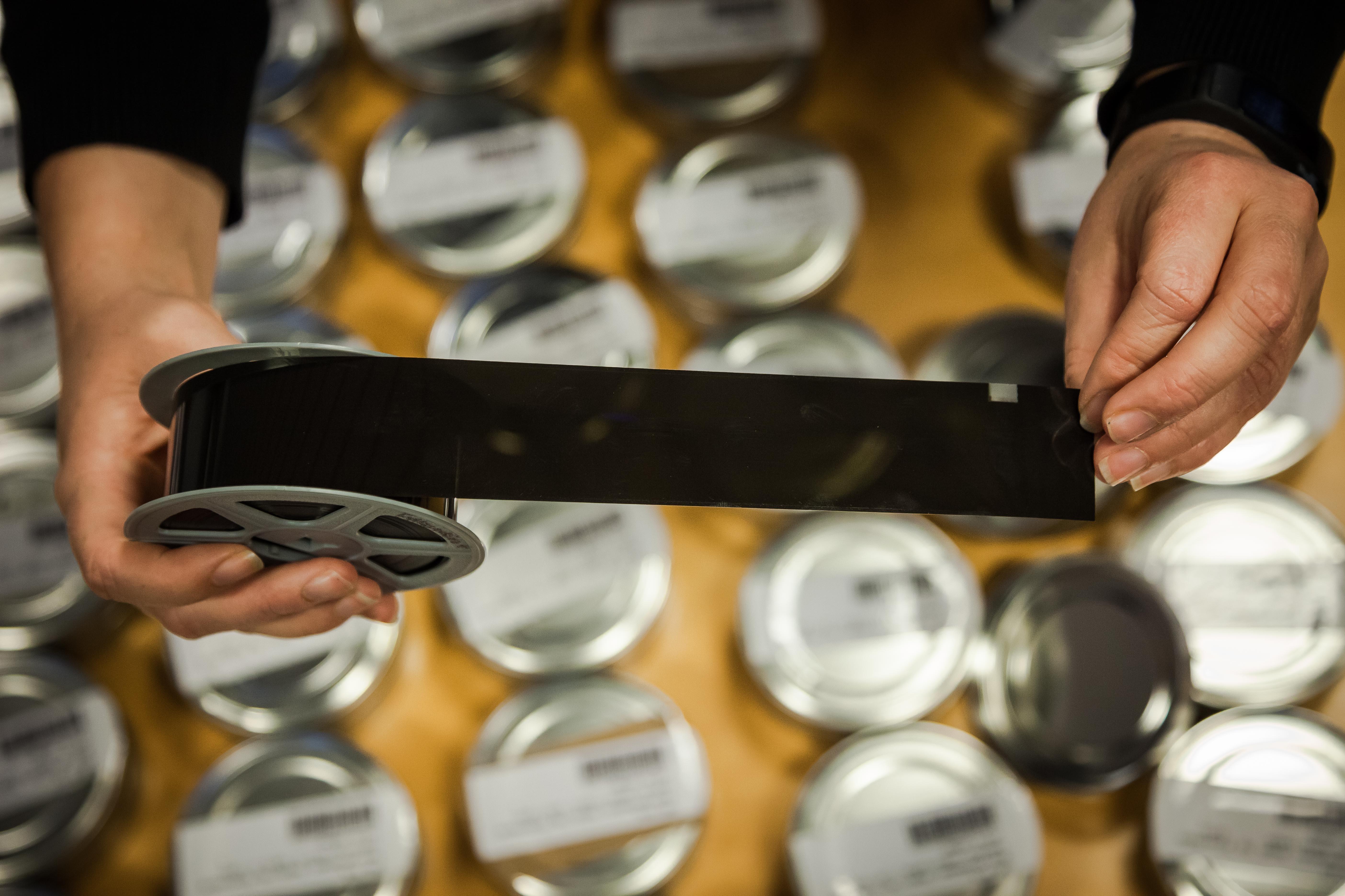 To hender held opp ein rull med mikrofilm som er rulla ut. Runde blikkboksar under henda.