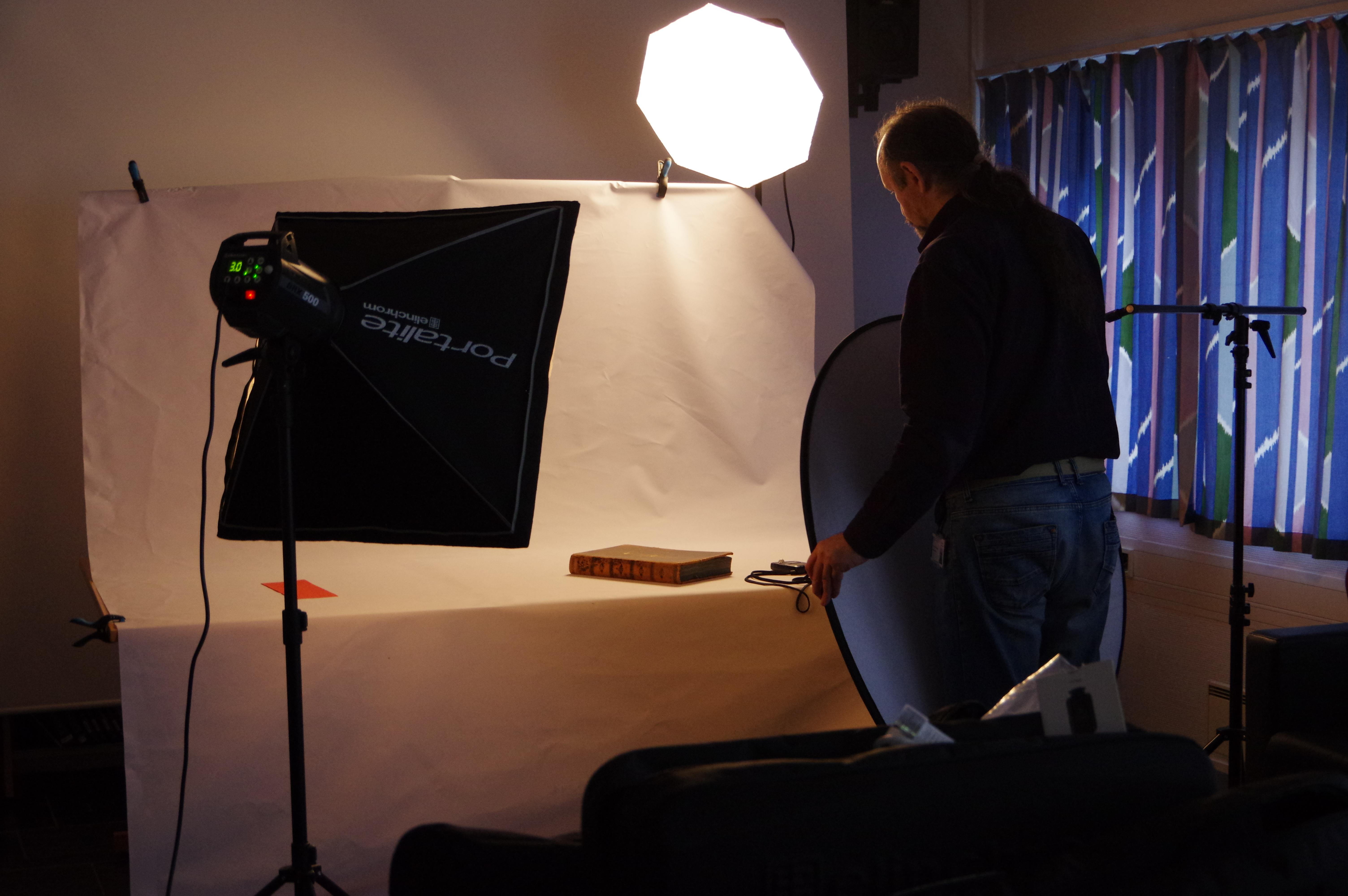 Mann står med kamera, ved kvitt bord med ein protokoll. Store lamper rundt.