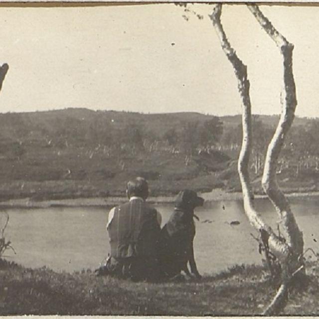 Mann og hund sit ved elvebreidd.