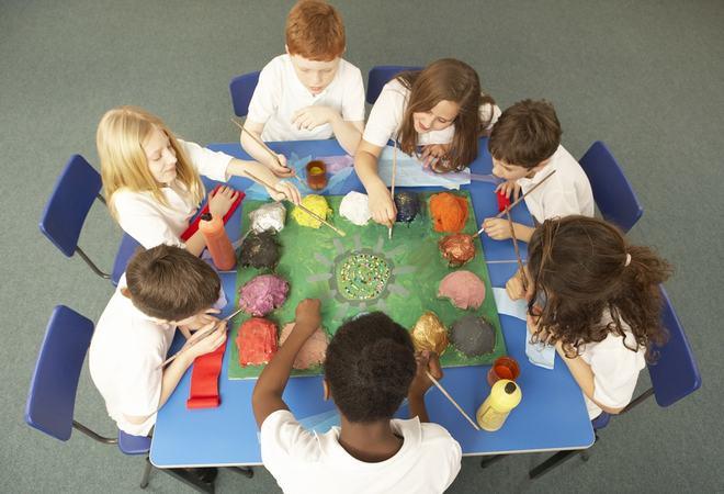 skulebarn sit sammen rundt eit bord