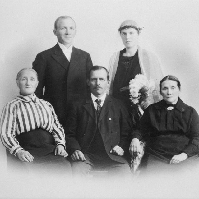 Svart/kvitt bilete av eit brudepar med tre familiemedlemmar