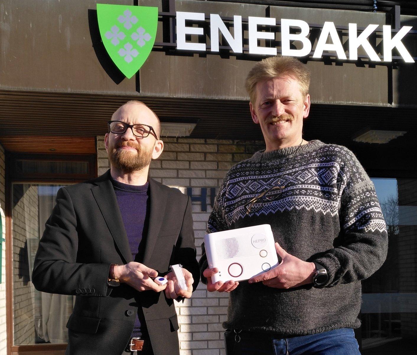 Velferdsteknologi - to menn foran kommunehuset holder en trygghetsalarm