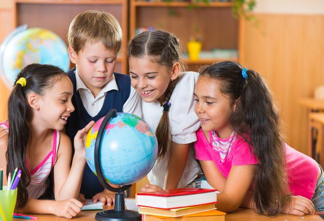 Portrait of cute schoolchildren looking at globe