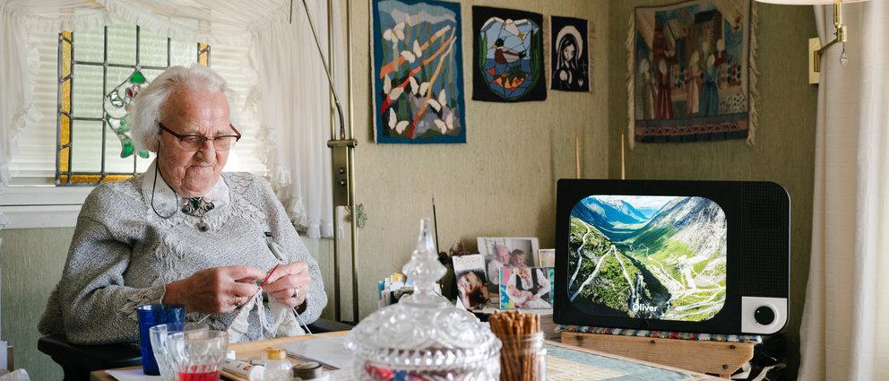 Gammel dame som strikker, med KOMP tv-skjerm ved kjøkkenbordet