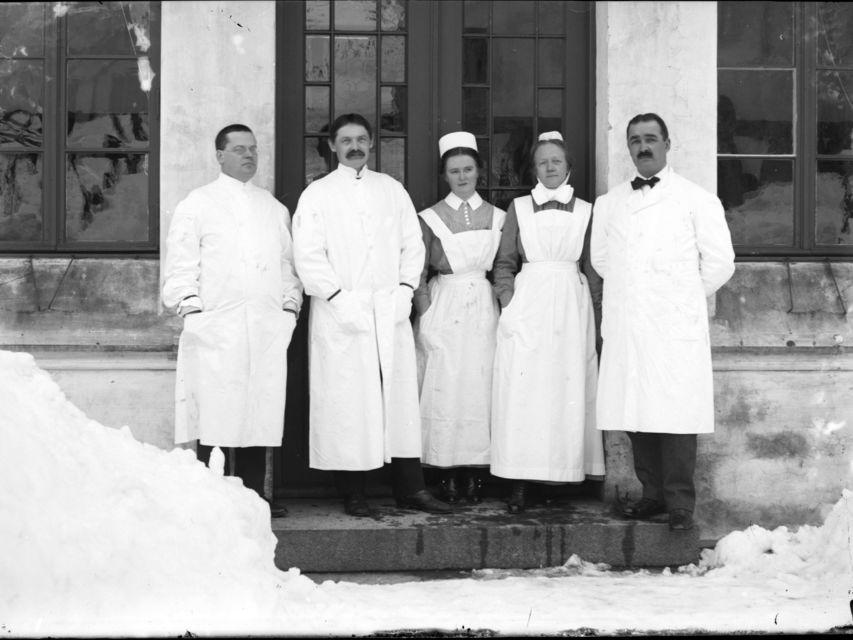 tre menn i legefrakk og to kvinner i sjukepleiaruniform foran eit hus. Mykje snø rundt dei