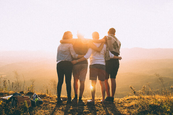 Canva - Four Person Standing on Cliff in Front of Sun