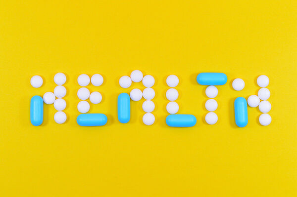 Canva - White and Blue Health Pill and Tablet Letter Cutout on Yellow Surface
