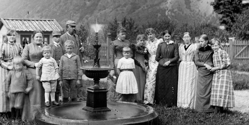 Gruppebilde 15 personar. Dei står rundt ei fontene