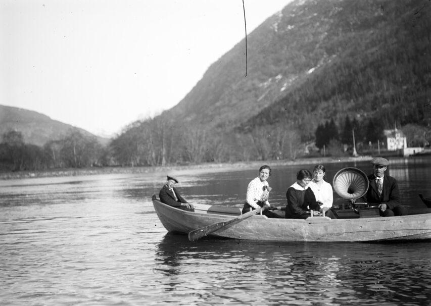 Fem personar, tre kvinner og to menn, i ein robåt på elva like nedanfor Hafstad Hotell. Hotellet i bakgrunnen. Med seg i båten har dei ein stor tutegrammofon