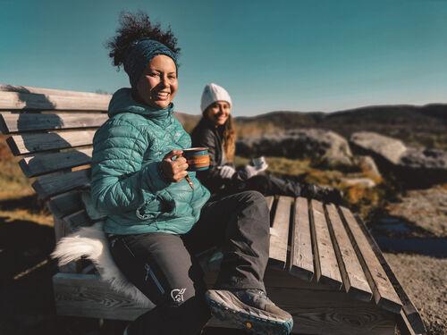 To kvinner på benk med kopp i hånden