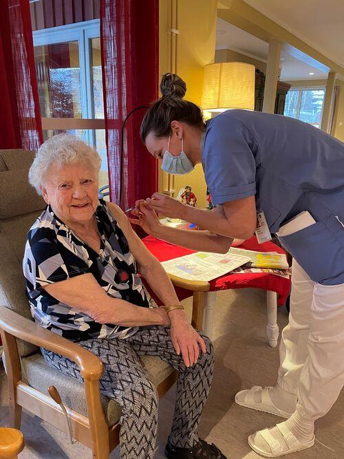 Anny Lervik mottar første vaksine av sykehjemslege Andrea Løvaas