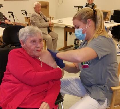 Turid Aas får første vaksinedose satt av avdelingssykepleier Stine Solberg Andersen. Foto: Vestby sykehjem, Vestby kommune