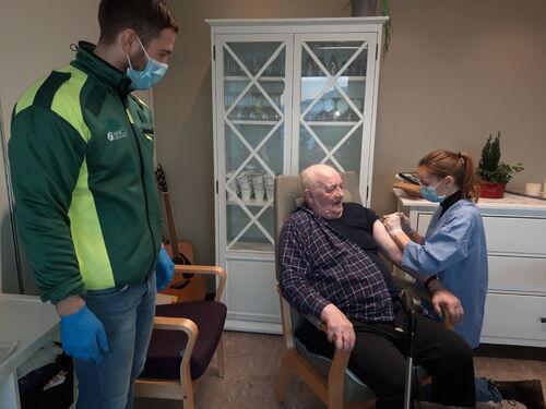 Bilde fra vaksinasjon på Liabø. Kristian Korsnes får vaksine av turnuslege Anne Grethe Gulla. Sykehjemslege Harald Grimstad bistår