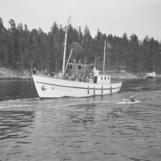 Bilete av ei redningsskøyte på vatnet, ikkje langt frå land. Dresskledde menn om bord, ein kano med to personar padlar attmed i vatnet.