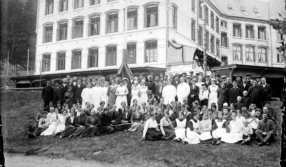 17.mai-feiring på Lyster sanatorium med pasientar, pleiepersonell og arbeidsfolk. Heilt til høgre sit familien Stuppelshaug med to eller tre born.