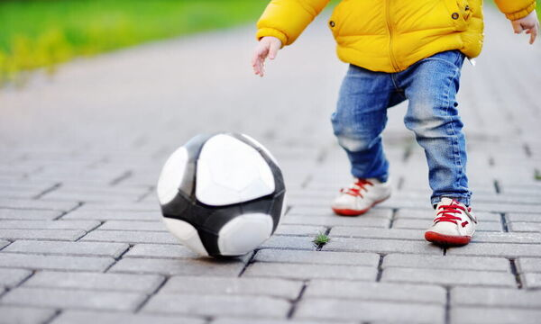 20846824-little-boy-having-fun-playing-a-soccer-ga