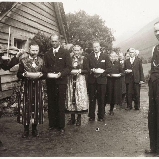 svart-kvitt-bilde av ei gruppe folk, menn i dress, damer i bunad, spelemann med fele til høgre.