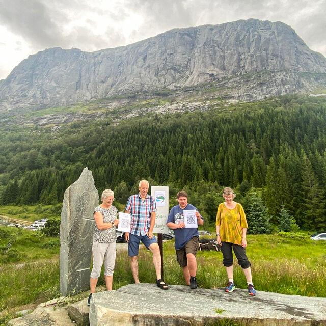 Fire personar poserer ved skilt, med natur og fjell i bakgrunnen.